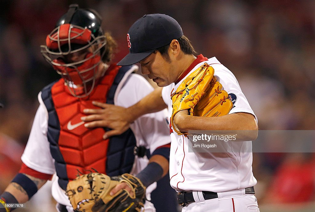 Koji Uehara #19 of the Boston Red Sox touches Jarrod Saltalamacchia #39 in the 9th inning after Uehara allowed the go-ahead run against the Baltimore Orioles in the 9th inning at Fenway Park on September 17 in Boston, Massachusetts.