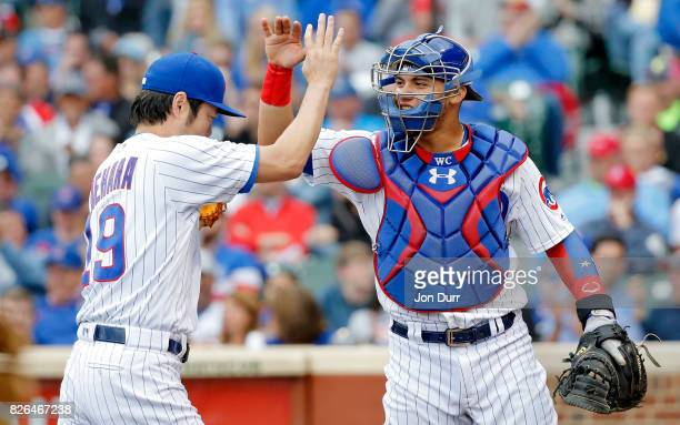 Koji Uehara of the Chicago Cubs and Willson Contreras high five at the end of the ninth inning at Wrigley Field on August 4 2017 in Chicago Illinois...