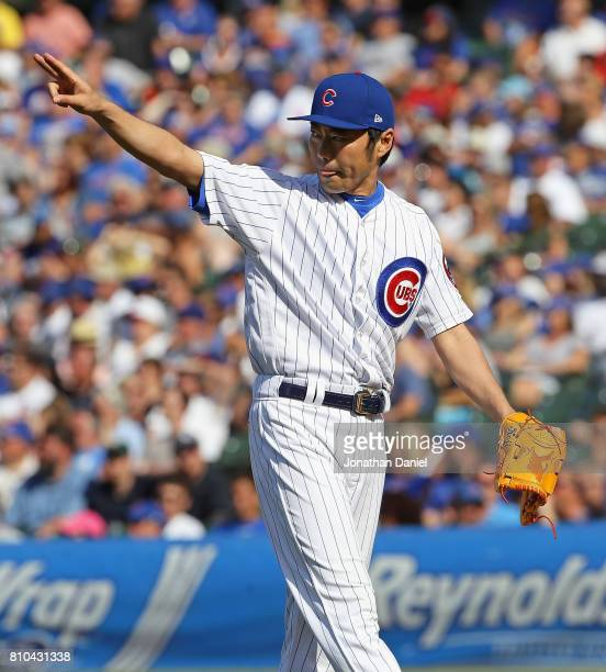 Koji Uehara of the Chicago Cubs points to a teammate after a catch in the outfield in the 8th inning against the Pittsburgh Pirates at Wrigley Field...