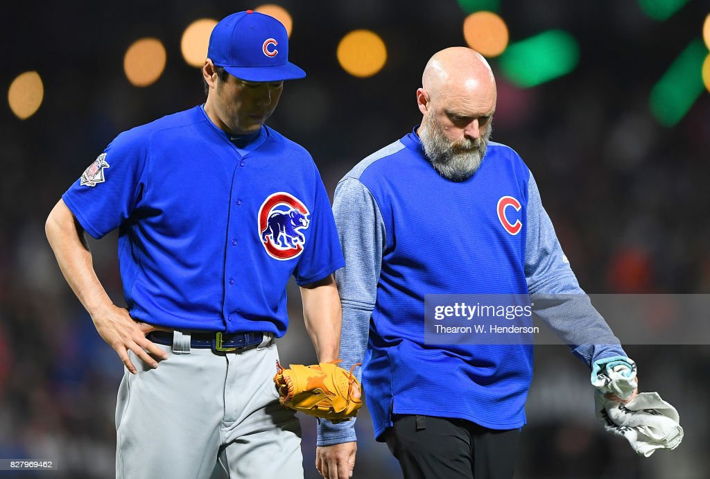 Koji Uehara #19 of the Chicago Cubs with an apparent injury is escorted off the field by trainer Ed Halbur during the bottom of the seventh inning against the San Francisco Giants at AT&T Park on August 8, 2017 in San Francisco, California.