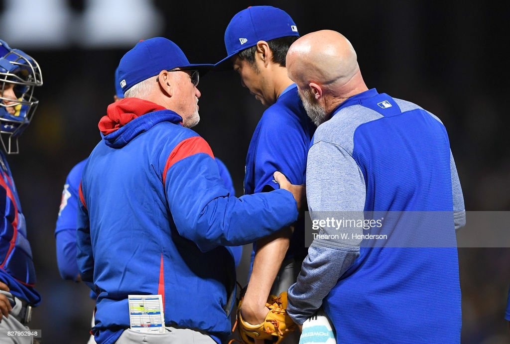 Koji Uehara #19 of the Chicago Cubs with an apparent injury is looked at by manager Joe Maddon and trainer Ed Halbur during the bottom of the seventh inning against the San Francisco Giants at AT&T Park on August 8, 2017 in San Francisco, California.