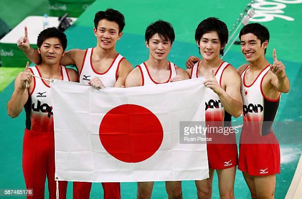 Koji Yamauro Yusuke Tanaka Kohei Uchimura Ryohei Kato and Kenzo Shirai of Japan pose for photographs after winning the gold medal during the men's...