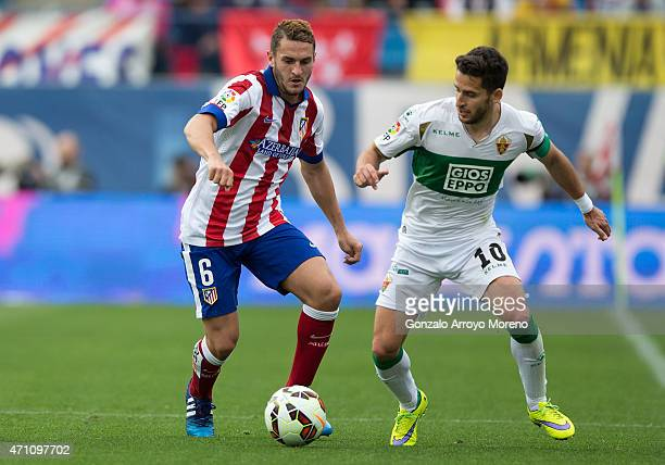 Koke of Atletico de Madrid competes for the ball with Ferran Corominas of Elche FC during the La Liga match between Club Atletico de Madrid and Elche...