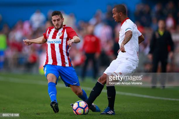 Koke of Atletico de Madrid competes for the ball with Mariano Ferreira of Sevilla FC during the La Liga match between Club Atletico de Madrid and...