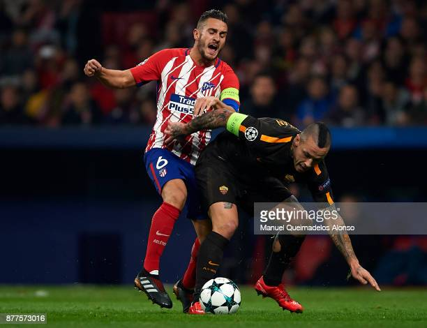 Koke of Atletico de Madrid competes for the ball with Radja Nainggolan of Roma during the UEFA Champions League group C match between Atletico Madrid...