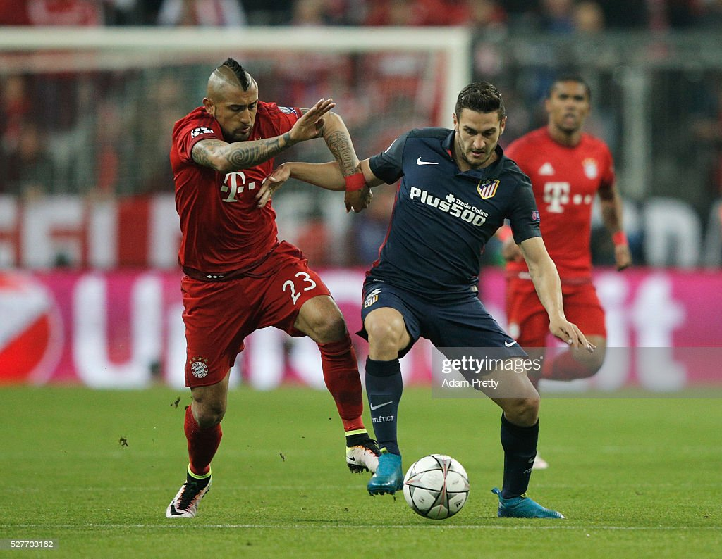 Koke of Atletico Madrid and Arturo Vidal of Bayern Munich battle for the ball during UEFA Champions League semi final second leg match between FC Bayern Muenchen and Club Atletico de Madrid at Allianz Arena on May 3, 2016 in Munich, Germany.