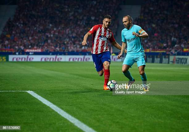Koke of Atletico Madrid competes for the ball with Andres Iniesta of Barcelona during the La Liga match between Atletico Madrid and Barcelona at...