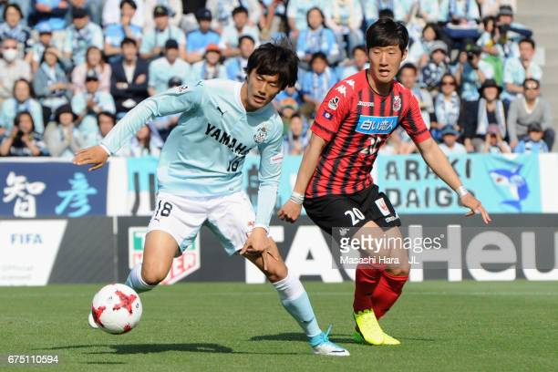 Koki Ogawa of Jubilo Iwata controls the ball under pressure of Kim Min Tae of Consadole Sapporo during the JLeague J1 match between Jubilo Iwata and...