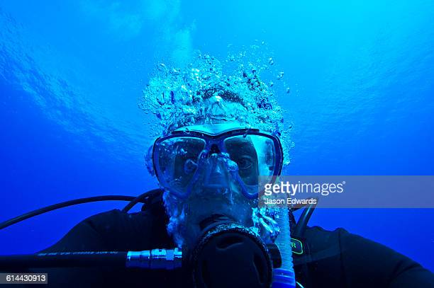 A scuba diver exhaling bubbles through his dive regulator.