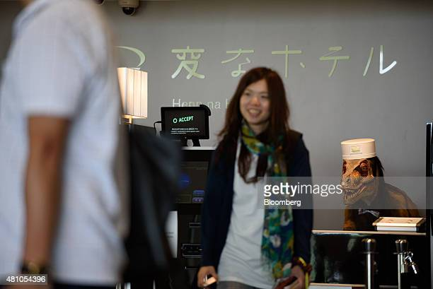 A Kokoro Company Ltd dinosaur robot stands at the reception desk as customers checkin at the Henn na Hotel operated by Huis Ten Bosch Co a unit of...