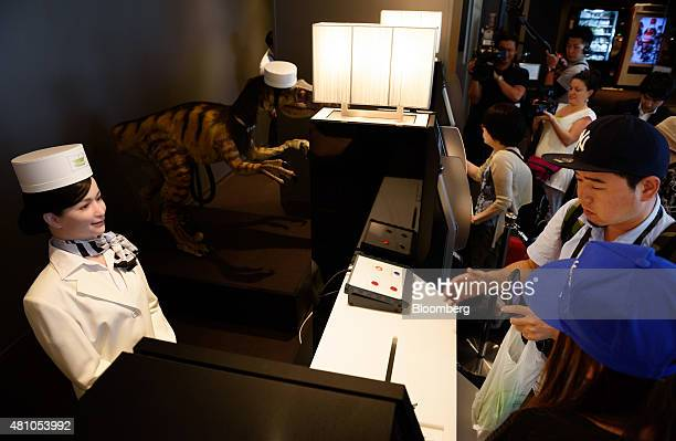 A Kokoro Company Ltd humanoid robot left and a dinosaur robot second left stand as customers gather at the reception desk of Henn na Hotel operated...