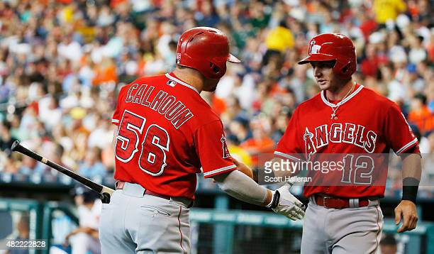 Kole Calhoun and Johnny Giavotella of the Los Angeles Angels of Anaheim celebrate after Giavotella scored a run in the first inning during their game...