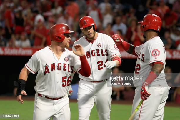 Kole Calhoun and Martin Maldonado congratulate CJ Cron of the Los Angeles Angels after he hit a threerun homerun during the first inning of a game...