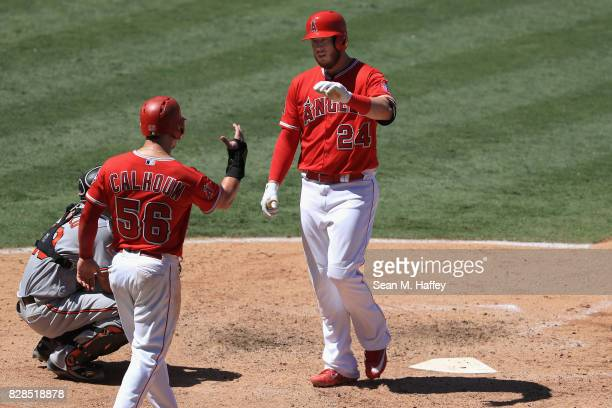 Kole Calhoun congratulates CJ Cron of the Los Angeles Angels of Anaheim after hitting a tworun homerun during the sixth inning of a game against the...