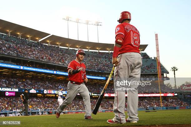 Kole Calhoun of the Los Angeles Angels celebrates with Martin Maldonado of the Los Angeles Angels after scoring off a single to right field by Yunel...