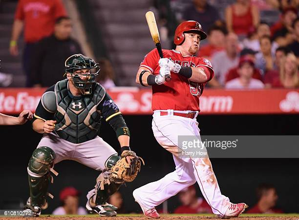 Kole Calhoun of the Los Angeles Angels hits a double during the fourth inning in front of Stephen Vogt of the Oakland Athletics at Angel Stadium of...