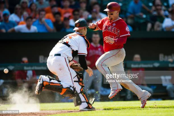 Kole Calhoun of the Los Angeles Angels of Anaheim avoids Caleb Joseph of the Baltimore Orioles as he scores a run on a RBI single hit by Cameron...