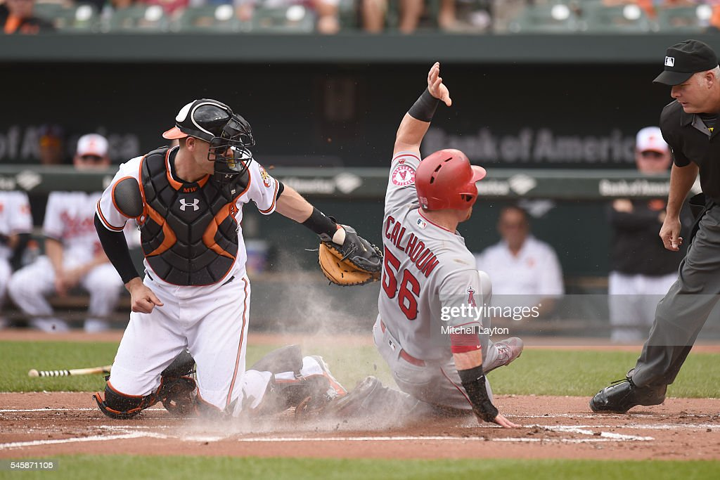 Kole Calhoun #56 of the Los Angeles Angels of Anaheim beats the tag by Matt Wieters #32 of the Baltimore Orioles on an umpires ruling in the first inning on a Mike Trout #27 (not pictured) triple during a baseball game at Oriole Park at Camden Yards on July 10, 2016 in Baltimore, Maryland.