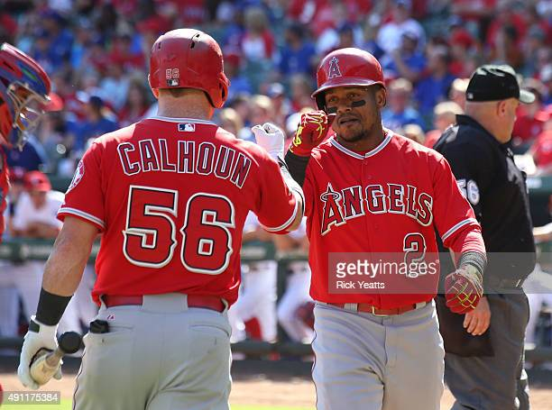 Kole Calhoun of the Los Angeles Angels of Anaheim congratulates Erick Aybar for hitting a solo home run in the ninth inning against the Texas Rangers...