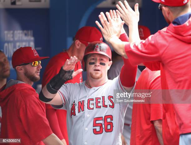 Kole Calhoun of the Los Angeles Angels of Anaheim is congratulated by teammates in the dugout after scoring a run in the ninth inning during MLB game...
