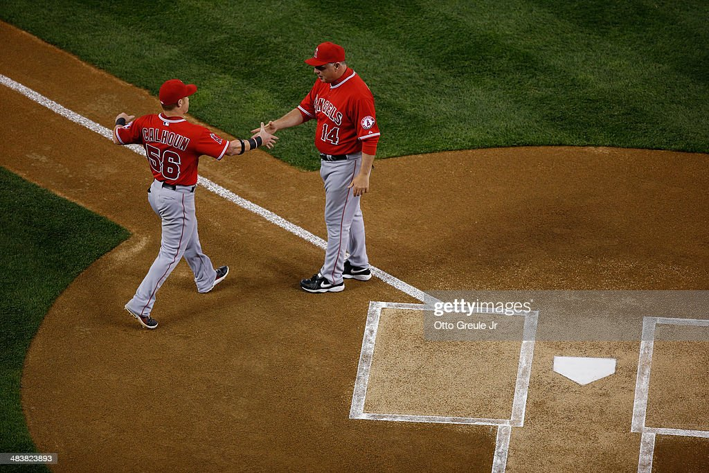 Kole Calhoun #56 of the Los Angeles Angels of Anaheim is greeted by manager Mike Scioscia #14 during introductions prior to the game against the Seattle Mariners on Opening Day at Safeco Field on April 8, 2014 in Seattle, Washington.