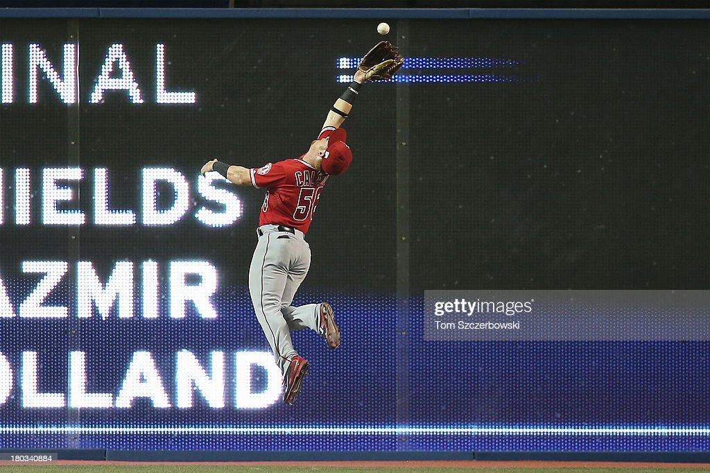 Kole Calhoun #56 of the Los Angeles Angels of Anaheim leaps after a bouncing ball that goes for a triple from <a gi-track='captionPersonalityLinkClicked' href=/galleries/search?phrase=Moises+Sierra&family=editorial&specificpeople=7509137 ng-click='$event.stopPropagation()'>Moises Sierra</a> #14 of the Toronto Blue Jays in the fourth inning during MLB game action on September 11, 2013 at Rogers Centre in Toronto, Ontario, Canada.
