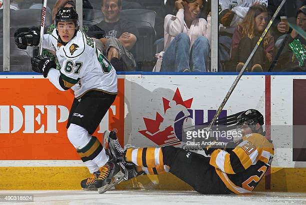Kole Sherwood of the London Knights slams Roland McKeown of the Kingston Frontenacs to the ice during an OHL game at Budweiser Gardens on September...