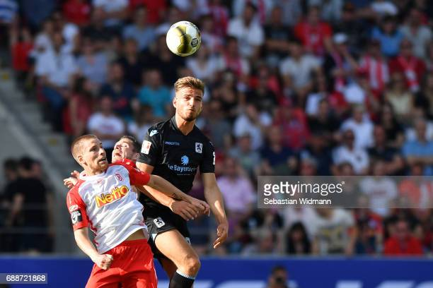 Kolja Pusch and Marco Gruettner of Jahn Regensburg jump for a header with Marin Pongracic of 1860 Muenchen during the Second Bundesliga Playoff first...