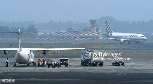 An Indian airport workers prepare an aircraft for flight as another parks beside it on the tarmac at the domestic terminal building of Netaji Subhas...