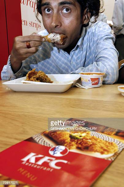 An Indian customer tastes a chicken preparation after the inauguration of a new KFC outlet in Kolkata 13 November 2006 The 140seat outlet located in...