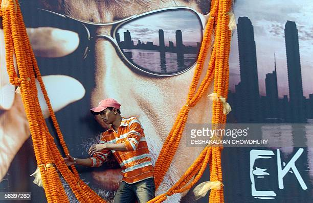 An Indian fan of Indian cinema icon Amitabh Bachchan places a huge garland on a promotional billboard for Bachchan's latest release 'Ek Ajnabi' on...