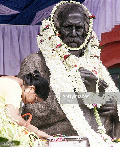 An Indian woman pays her respects beside a statue of nobel laureate Rabindranath Tagore in Kolkata 09 May 2007 during celebrations surrounding...