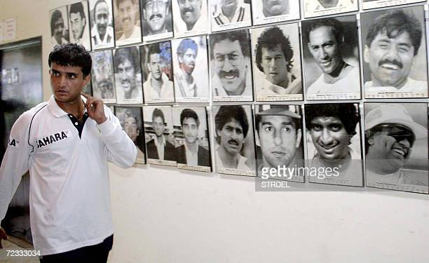 Former Indian cricket captain Sourav Ganguly walks past a wall featuring images of national and international cricketing legends including himself as...