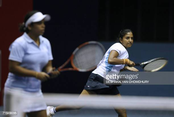 Indian tennis player Archana Venkataraman is watched by her pertner Ragini Vimal as she plays a stroke during a prequarterfinal round match against...