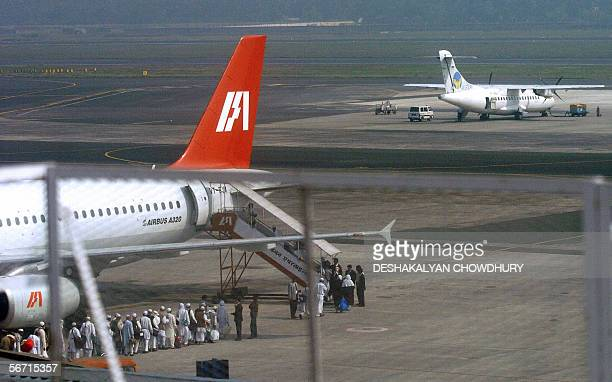 Passengers of an Indian Airlines Airbus stand in line on the tarmac as they wait to board the aircraft by a tractor stairway due to the...