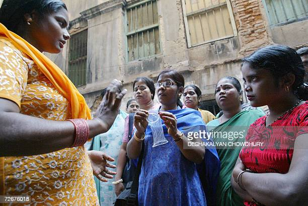 TO GO WITH 'HEALTHAIDSINDIAPHARMA' Indian sex workers listen to a volunteer as she demonstrates how to use a female condom at Soanagachi Kolkata's...