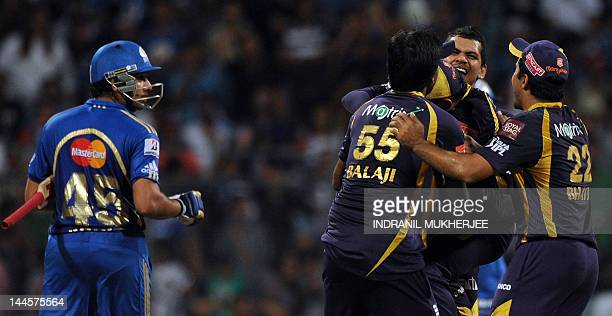 Kolkata Knight Riders cricketers congratulate teammate Sunil Narine after taking the wicket of Mumbai Indians batsman Rohit Sharma during the IPL...
