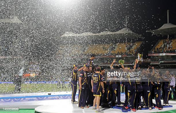 Kolkata Knight Riders cricketers support staffs and officials celebrate with the DLF IPL trophy after winning the IPL Twenty20 cricket final match...