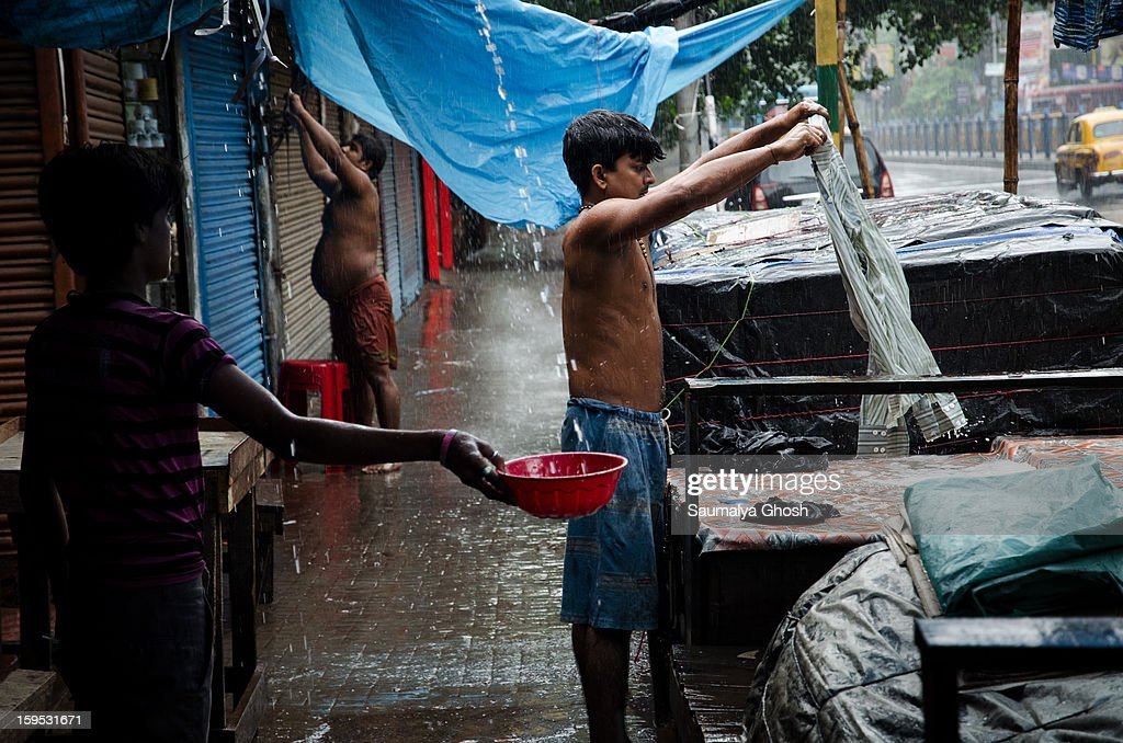 Kolkata street scene in a rainy day. A dhobi (laundry man) is washing clothes and a boy is collecting water in a pot.