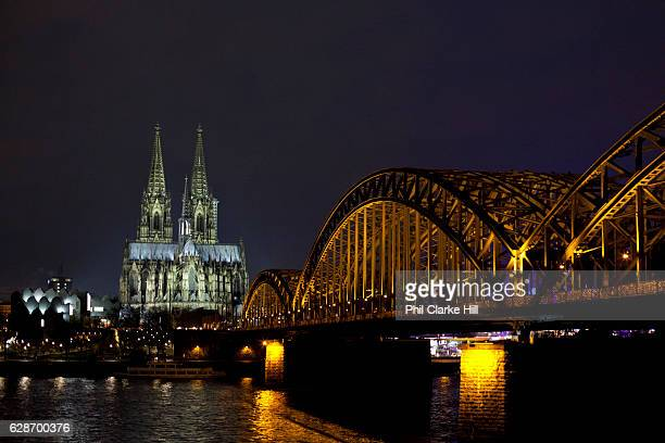 Koln Cologne Dom Cathedral and the Hohenzollern Bridge illuminated at night Cologne Germany