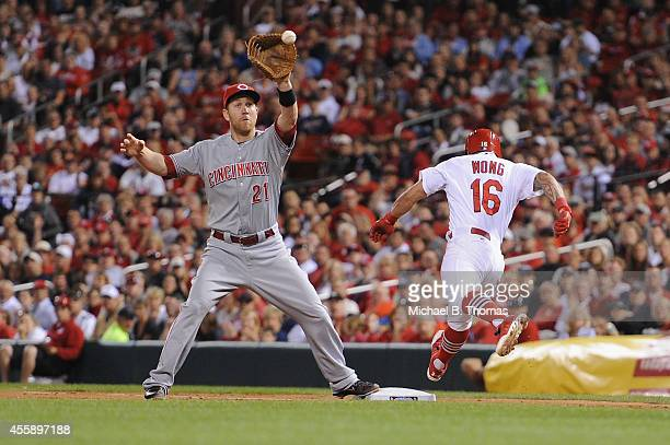 Kolten Wong of the St Louis Cardinals attempts to beat the throw to first base against Todd Frazier of the Cincinnati Reds in the third inning at...