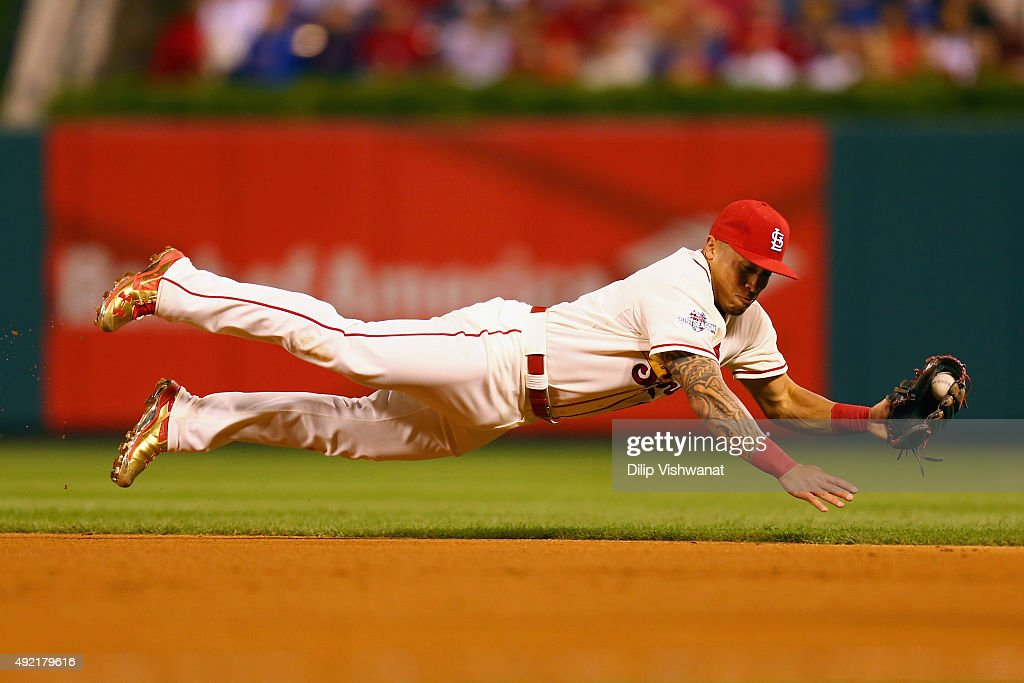 Kolten Wong #16 of the St. Louis Cardinals dives to field a ground ball in the ninth inning against the Chicago Cubs during game two of the National League Division Series at Busch Stadium on October 10, 2015 in St Louis, Missouri.