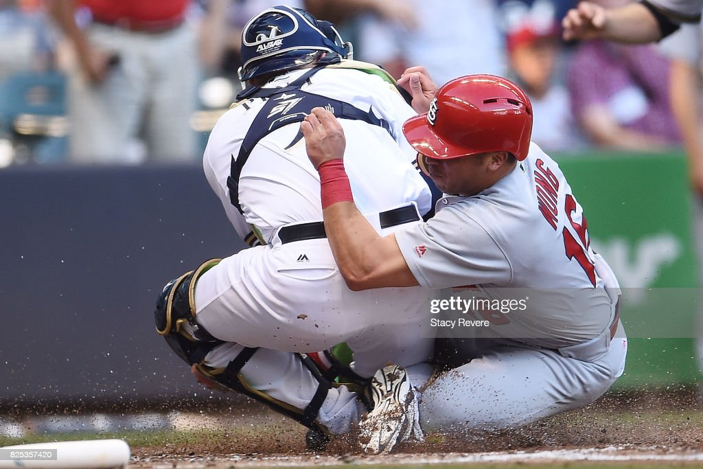 Kolten Wong #16 of the St. Louis Cardinals is tagged out at home plate by Manny Pina #9 of the Milwaukee Brewers during the third inning of a game at Miller Park on August 1, 2017 in Milwaukee, Wisconsin.