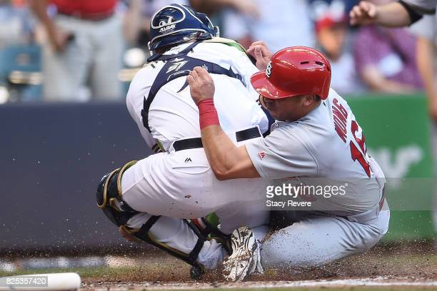 Kolten Wong of the St Louis Cardinals is tagged out at home plate by Manny Pina of the Milwaukee Brewers during the third inning of a game at Miller...