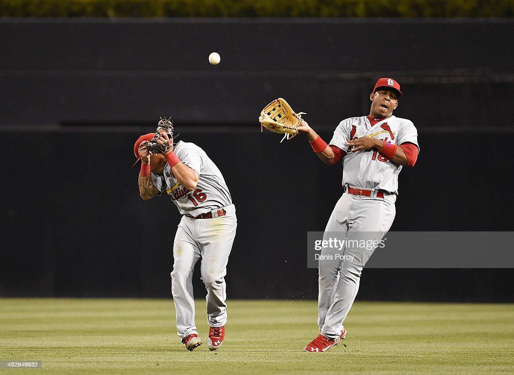 Kolten Wong #16 of the St. Louis Cardinals, left, and Oscar Taveras #18 misplay a double hit be Alexi Amarista #5 of the San Diego Padres during the third inning of a baseball game at Petco Park July 30, 2014 in San Diego, California.