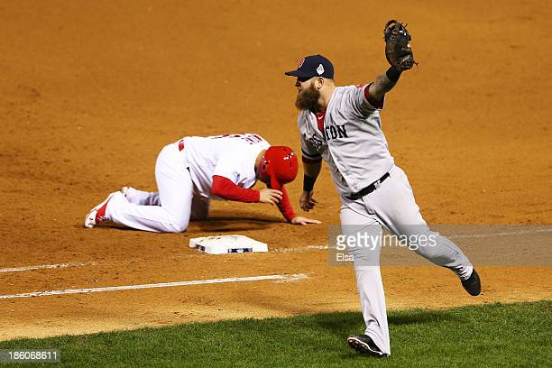 Kolten Wong of the St Louis Cardinals reacts after being tagged out at first by Mike Napoli of the Boston Red Sox on a pick off play by Koji Uehara...