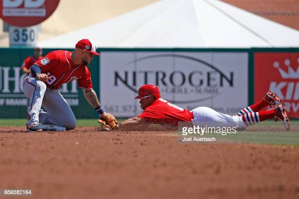 Kolten Wong of the St Louis Cardinals steals secon base under the tag by Brandon Snyder of the Washington Nationals in the second inning during a...