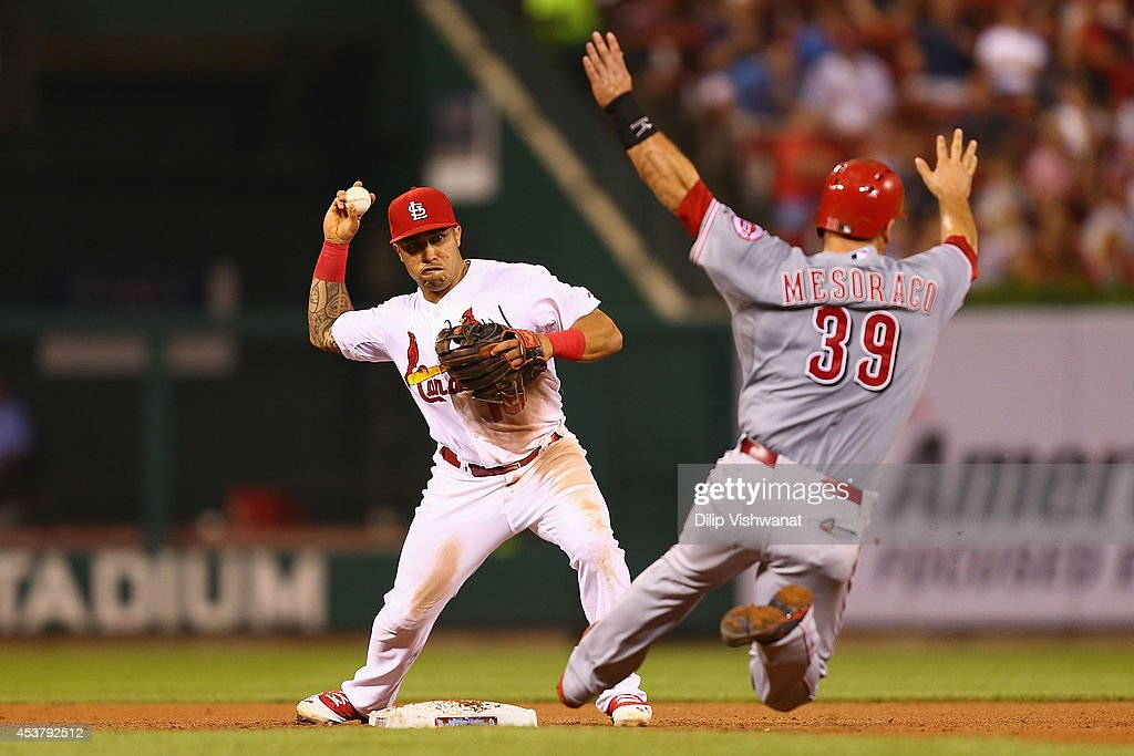 Kolten Wong #16 of the St. Louis Cardinals turns a double play against Devin Mesoraco #39 of the Cincinnati Reds in the fourth inning at Busch Stadium on August 18, 2014 in St. Louis, Missouri.