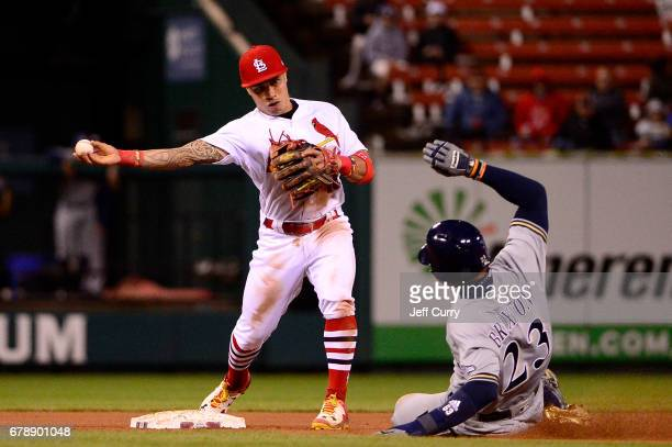 Kolten Wong of the St Louis Cardinals turns a double play as Keon Broxton of the Milwaukee Brewers slides during the seventh inning at Busch Stadium...