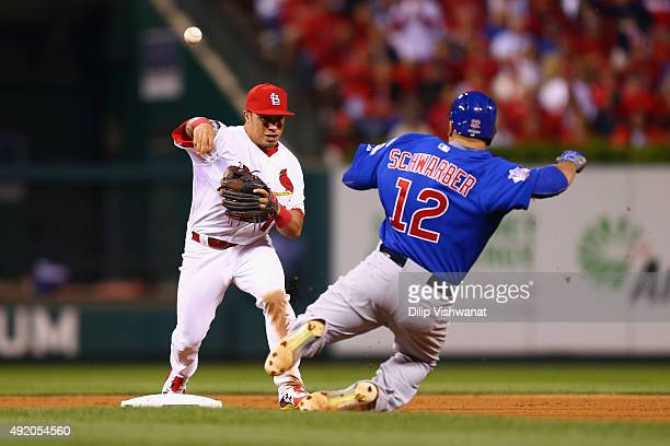 Kolten Wong of the St Louis Cardinals turns a double play over Kyle Schwarber of the Chicago Cubs in the fourth inning during game one of the...